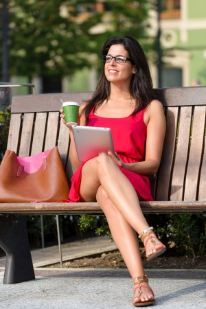 Businesswoman reading on tablet pc computer and drinking coffee on a work break in european city square  Woman sitting on a park bench relaxing with ebook before job  photo