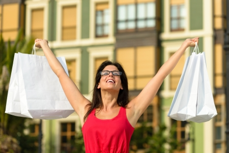 outstretching: Blissful fashion woman raising white shopping bags and enjoying the commercial store sales in european city square. Happy caucasian fashion brunette after buying clothes.