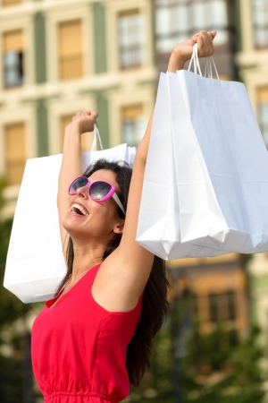 outstretching: Blissful fashion woman raising white shopping bags and enjoying the commercial store sales in european city square. Happy caucasian brunette after buying clothes. Stock Photo