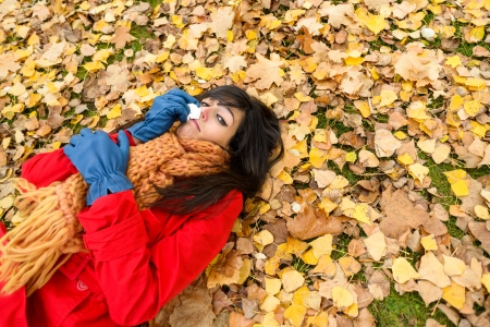 Sick sad woman with flu or cold crying and blowing her nose with a tissue in autumn  because  Autumnal illness and depression  Caucasian brunette in warm red coat