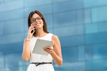 비즈니스 여자 디지털 통신 기술을 사용하여 태블릿 pc 컴퓨터를 들고와 그녀의 일을 회사 건물 백인 히스패닉 여성 임원 이외의 휴대 전화에 전화
