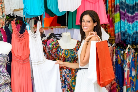 bargain for: Woman shopping summer colorful dresses and clothes in street market  Tourist shopper looking for bargain clothing and sales  Stock Photo