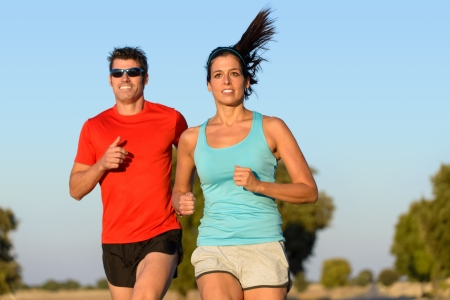Fitness couple running in country road  Cheerful runners training outdoors on summer for sport and healthy lifestyle