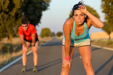 sudoroso: Cansado pareja aptitud de los corredores de la sudoraci�n y de tomar un descanso durante el entrenamiento de marat�n en la carretera nacional atletas sudorosos despu�s de correr duro Foto de archivo