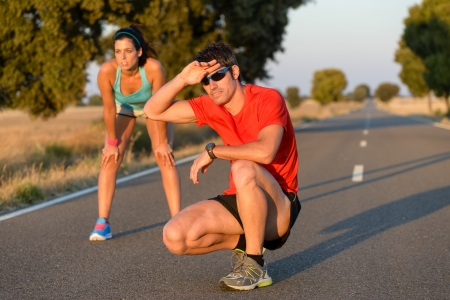 Tired fitness couple of runners sweating and taking a rest during marathon training in country road  Sweaty athletes after running hard  photo