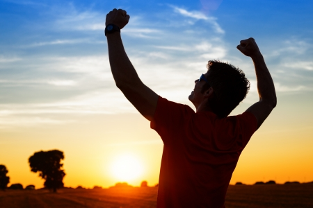 back lighting: Successful sportsman raising arms on golden sky back lighting sunset summer after cross running  Fitness male athlete with arms up celebrating goals after sport exercising and working out outdoors