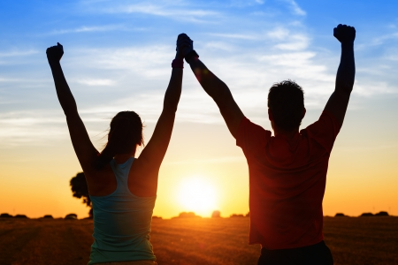 Successful couple of young athletes raising arms to golden summer sunset sky after training  Fitness man and woman with arms up celebrating sport goals after exercising in countryside field
