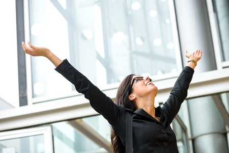 Business female executive success. Successful and blissful woman outside corporate building. Successful and happy hispanic brunette businesswoman with arms up. Stock Photo