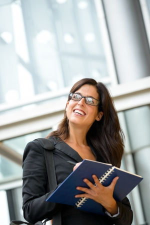 taking notes: Successful confident businesswoman or secretary taking notes in a notebook. Happy caucasian business entrepreneur woman writing on agenda outside corporate building. Stock Photo