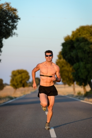Man running with hearth rate monitor in countryside road. Fit muscular torso male athlete training for marathon run. photo