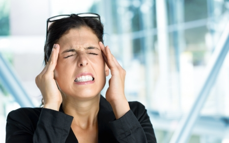 Business woman headache or anxiety attack crisis. Businesswoman suffering painful migraine or stress in work. Stock Photo