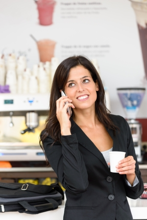 Cheerful hispanic business woman talking on the phone in cafe. Successful executive businesswoman or entrepreneur on a working break in coffee shop. photo