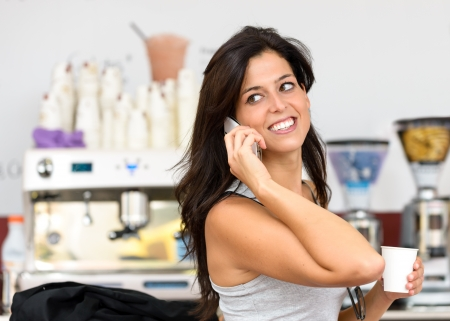 Cheerful hispanic business woman talking on the phone in cafe. Successful casual executive businesswoman or entrepreneur on a working break in coffee shop. photo