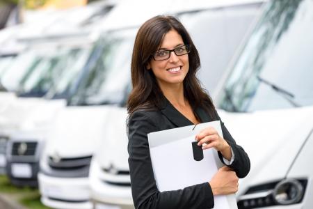 Succesvolle verkoop zakelijke vrouw in busje transport beurs. Commerciële tentoonstelling en verhuur concept car. Mooie vrouwelijke verkoper of verkoper houden autosleutels.
