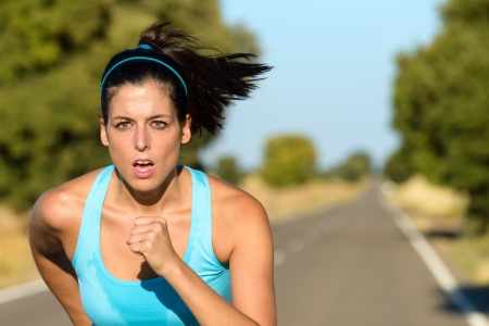 Sweaty female athlete running on rural road. Hispanic woman training sprint and exercising hard for intense marathon. Stock Photo