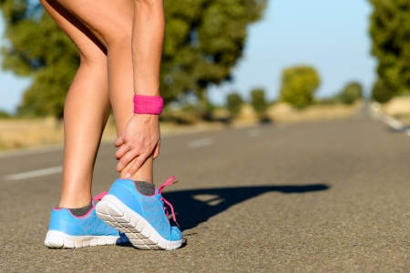 leg injury: Sport running ankle sprain. Sportswoman touching painful twisted or broken ankle. Athlete runner training accident. Stock Photo