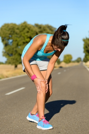 Running sport knee injury. Woman runner in pain while training for marathon in country road. Caucasian female athlete. Stock Photo