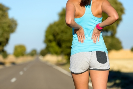 back training: Female runner athlete low back injury and pain. Woman suffering from painful lumbago while running in rural road. Stock Photo