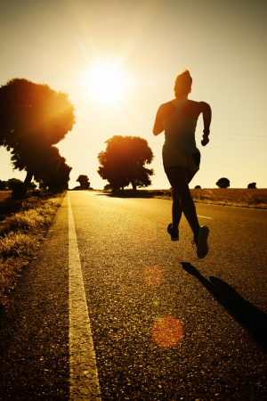 joggers: Woman running marathon on beautiful golden summer sunset background in rural road. Female athlete fitness girl training and exercising towards the bright light of sun. Stock Photo