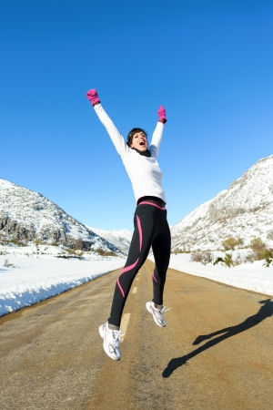 outstretching: Happy woman jumping celebrating victory on winter mountain road