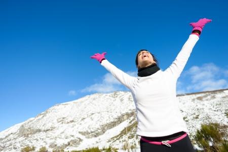 happy successful woman raising arms in winter sportswear  photo