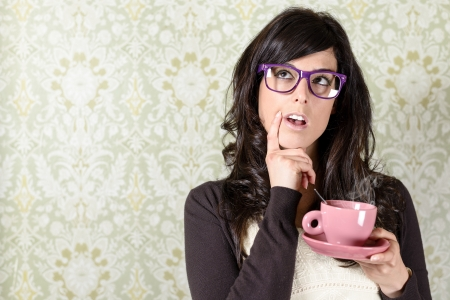 Undecided woman thinking for making a decision on floral vintage wall background  Retro pensive girl holding steaming cup of coffee at home