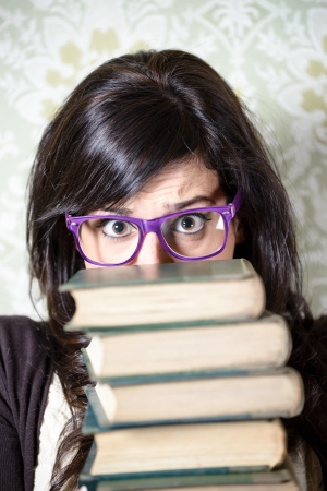 hispanic students: Studying woman stress  Young overwhelmed female student holding a pile of old books  Girl with glasses looking upset  Stock Photo