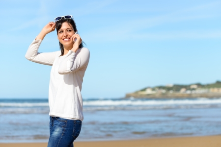 Woman calling by cell phone and walking on beach  Brunette woman on travel vacation mobile conversation smiling  photo