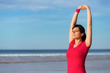 Fitness woman stretching for warming up before exercising  Brunette beautiful girl doing relaxing and breathing exercise on the beach  Caucasian fit model on sea copy space background  photo
