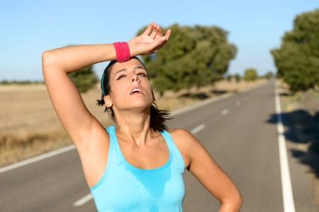田舎道でハードを実行した後発汗疲れたランナー。暑い夏はマラソンのトレーニングの後に疲れ汗女性。屋外ヒスパニックのブルネット女性の選手 写真素材