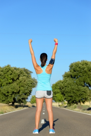 female athlete: Female runner success. Woman raising arms for motivation before running in countryside road. Winner athlete training.