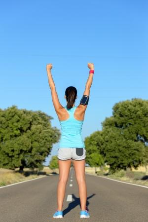 mujer deportista: Mujer éxito corredor. Mujer que levanta los brazos para la motivación antes de correr en carretera rural. Entrenamiento de un atleta ganador. Foto de archivo