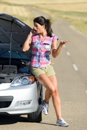 Angry and desperate woman calling to insurance assistance service after car accident  Upset woman on cellphone discussion explaining broken down auto engine  photo
