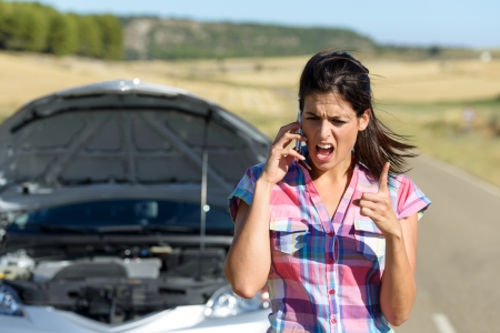 Angry and desperate woman calling to insurance assistance service after car accident  Upset woman on cellphone discussion explaining broken down auto engine