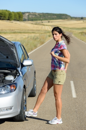 car trouble: Upset woman kicking car wheel after car accident or broken down engine waiting for insurance road assistance service help  Stock Photo