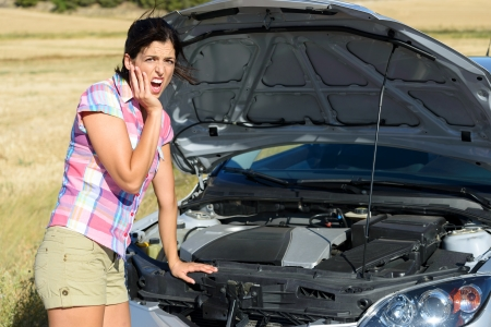 road assistance: Upset woman after car accident or broken down engine waiting for insurance road assistance service help
