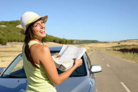 Young woman on car road travel looking map  Brunette hispanic girl having fun on summer journey  photo