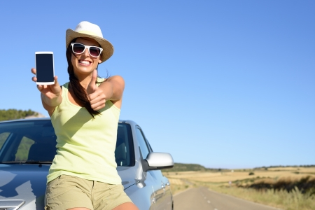 Young woman leaning on car showing cell phone screen and doing thumbs up gesture  Positive woman giving her approval to car insurance service