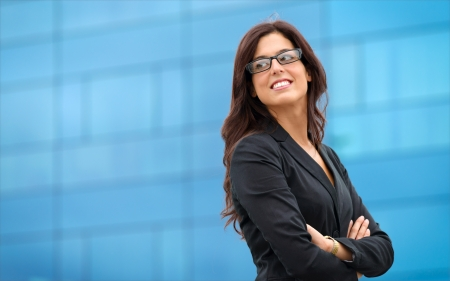 Businesswoman in leadership confident pose outside corporate building  Business woman crossing arms and smiling  Stock Photo