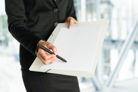 Businesswoman pointing blank empty sheet with pen for data space. Business concept. photo