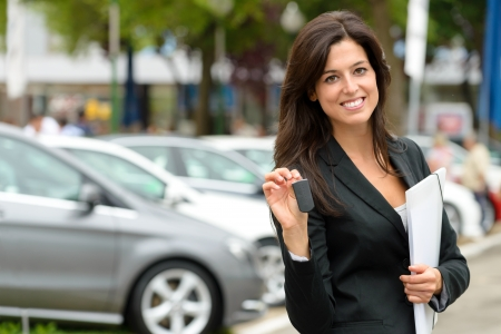 Female car seller holding car keys  Caucasian saleswoman in luxury vehicle trade fair  Auto rental or sales concept  photo