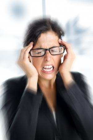 stressing: Businesswoman with intense stress and painful headache  Woman with glasses in job problems  Stock Photo