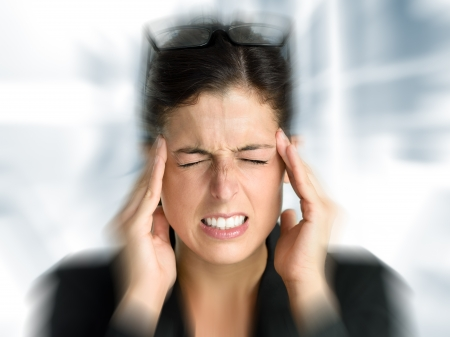 Businesswoman with intense stress and painful headache  Woman in job problems