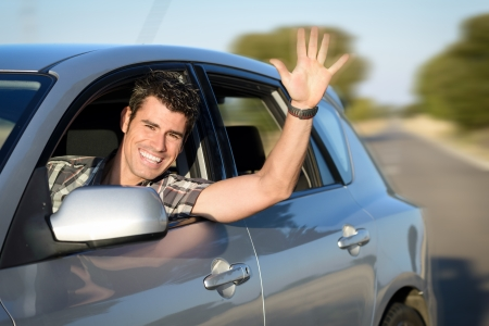 Man in car driving and waving  Male driver having fun traveling on road trip  Stock Photo