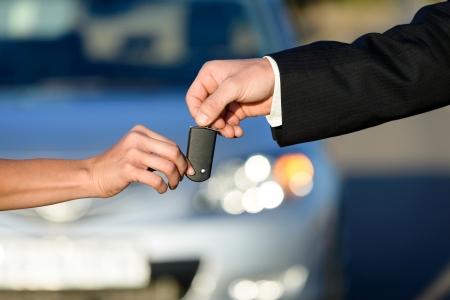 車のセールスマンの女性バイヤー新車販売またはレンタル コンセプトにキーを与える