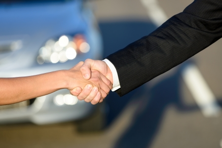 Man and woman closing a car sale agreement with a handshake  Salesman and buyer shaking hands photo