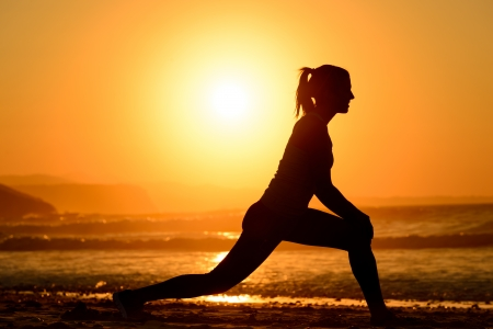 Woman practicing yoga, stretching and relaxing exercises on the beach at sunset  Female athlete silhouette exercising on towards the sea on bright golden sun background  photo
