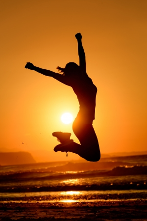 Successful woman jumping, dancing and having fun on sunset in beach  Freedom and happiness concept  Girl celebrating work out success  Banco de Imagens