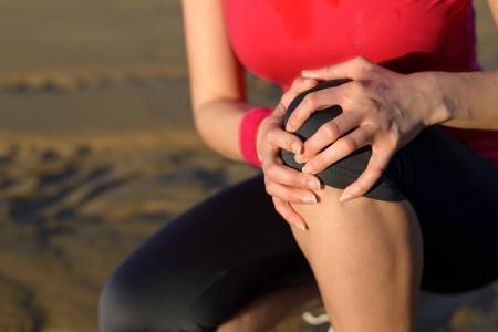 dolor de rodilla: Runner deporte lesi�n de rodilla Mujer en dolor mientras se ejecuta en la playa cauc�sica atleta femenina con r�tula dolorosa