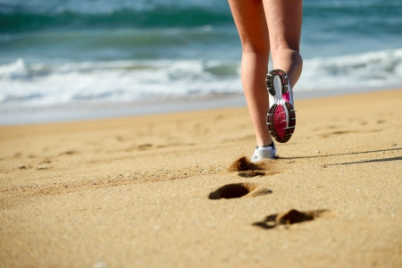 Woman running on beach  Sport footwear, sand footprints and legs close up  Runner feet detail